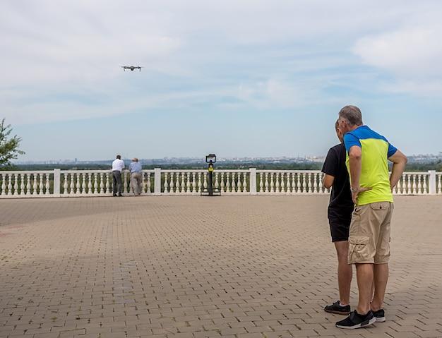 Mężczyźni odpalają drona i robią zdjęcia. lato na nabrzeżu w mieście. wywiad w mieście.