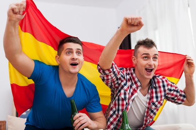 Mężczyźni oglądają mecz piłki nożnej w telewizji i kibicują hiszpańskiej drużynie