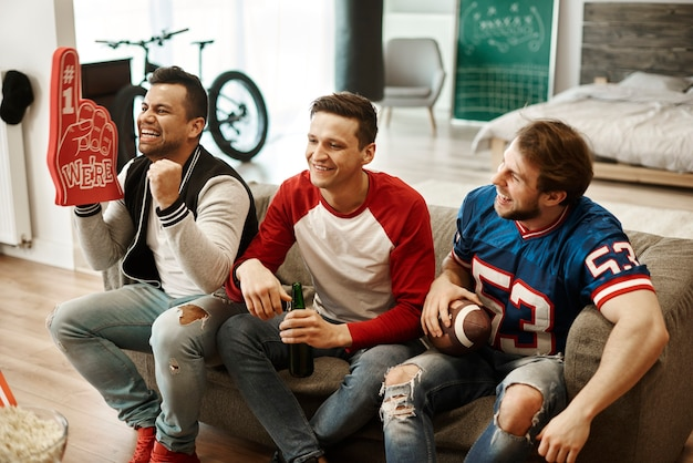 Mężczyźni oglądający mecz w salonie