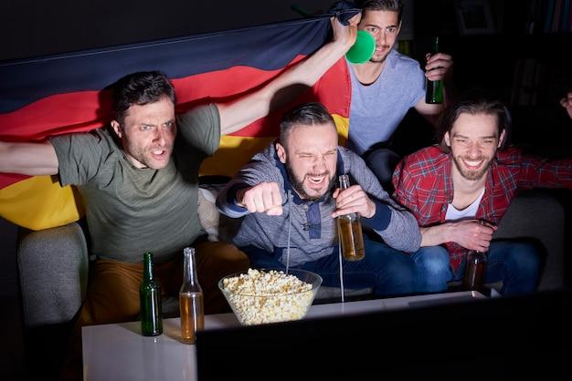 Mężczyźni oglądający mistrzostwa w telewizji