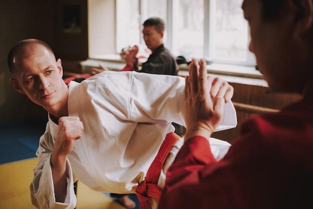 Mężczyźni opracowują technikę uderzenia na siłowni.