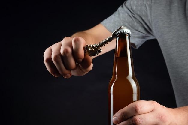 Mężczyźni otwierający zimną butelkę piwa otwieraczem do butelek