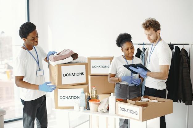 Mężczyźni pakujący pudełko. afrykańska dziewczyna wolontariuszka. pomoc humanitarna dla ludzi.
