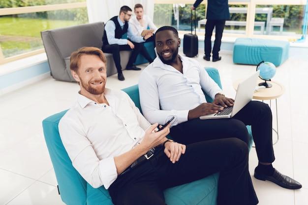 Mężczyźni patrzą na smartfony, jeden z nich ma laptopa