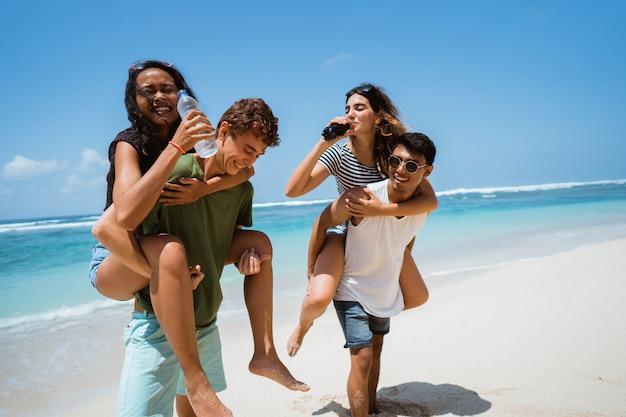 Mężczyźni piggybacking kobiet posiadających butelki softdrink