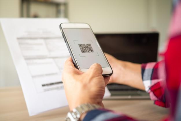 Mężczyźni płacą roczne ubezpieczenie na życie za pośrednictwem aplikacji bankowych przez telefon.
