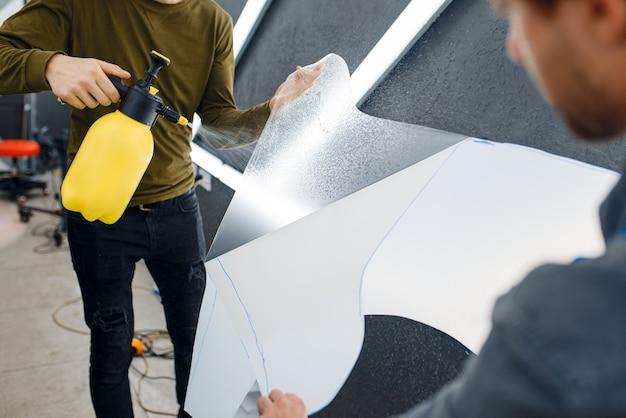 Mężczyźni pracownicy zwilżają folię samochodową przed nałożeniem. montaż powłoki chroniącej lakier samochodu przed zarysowaniami. nowy pojazd w garażu, procedura tuningu