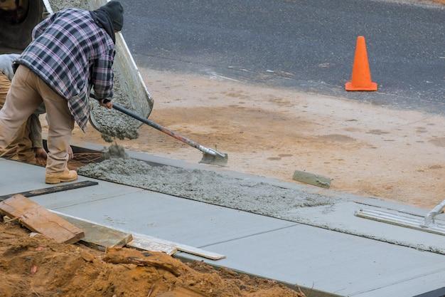 Mężczyźni pracujący na nowym betonowym podjeździe w domu mieszkalnym