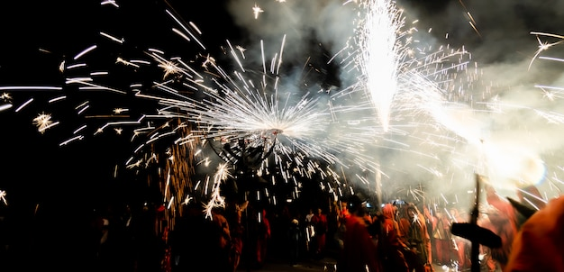 Mężczyźni przebrani za diabły bawiące się fajerwerkami