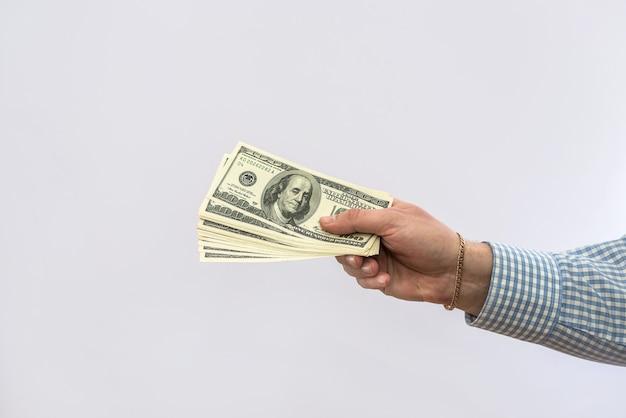 Mężczyźni ręka trzymają nas pieniądze na białym tle, koncepcja finansów