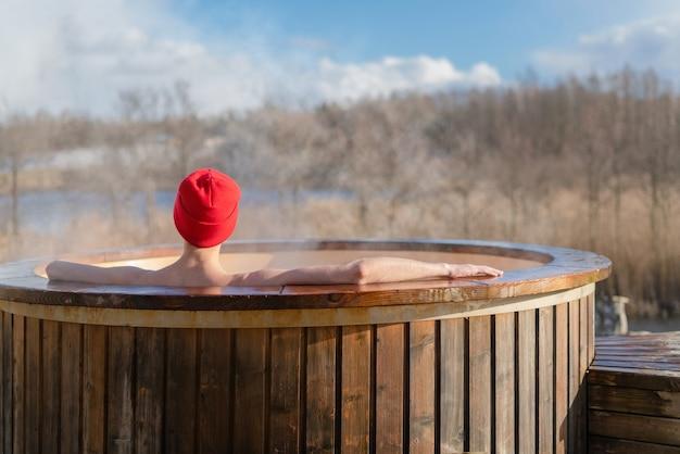 Mężczyźni relaksujący się w drewnianej wannie z hydromasażem na zewnątrz.