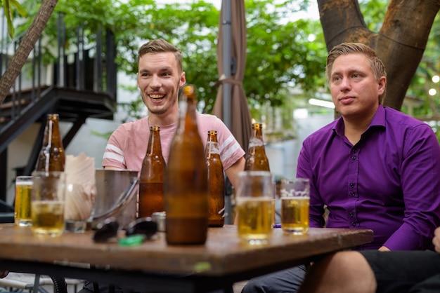 Mężczyźni rozmawiają i śmieją się podczas picia piwa na świeżym powietrzu