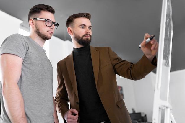 Mężczyźni rozmawiają o projekcie pracy