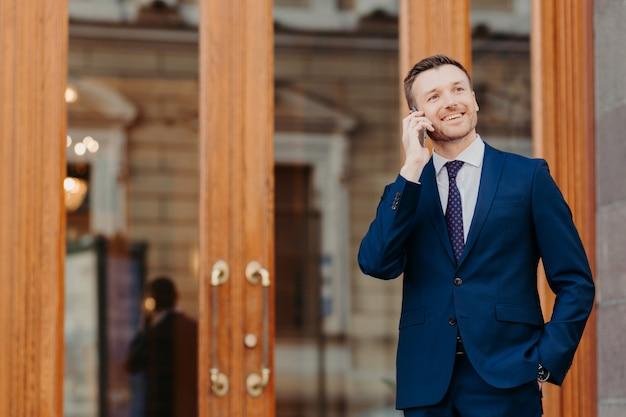 Mężczyźni rozmawiają przez telefon na ulicy, ubrani w formalny garnitur, trzymają rękę w kieszeni