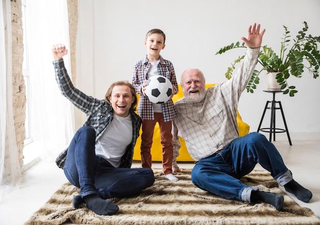Mężczyźni różnych pokoleń oglądający piłkę nożną