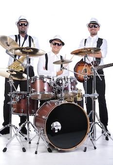 Mężczyźni siedzą przy grających na nich instrumentach.