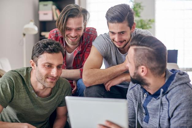 Mężczyźni siedzą w salonie i surfują po internecie