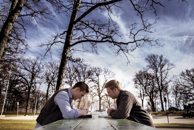 Mężczyźni siedzący na ławce z bibliami i modlący się w ogrodzie w słońcu z rozmytym tłem