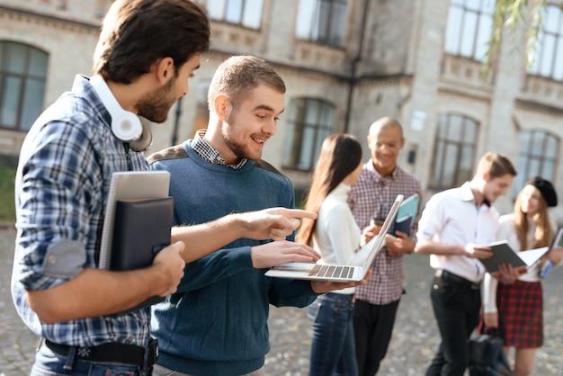 Mężczyźni stoją razem na ulicy w słoneczny dzień.