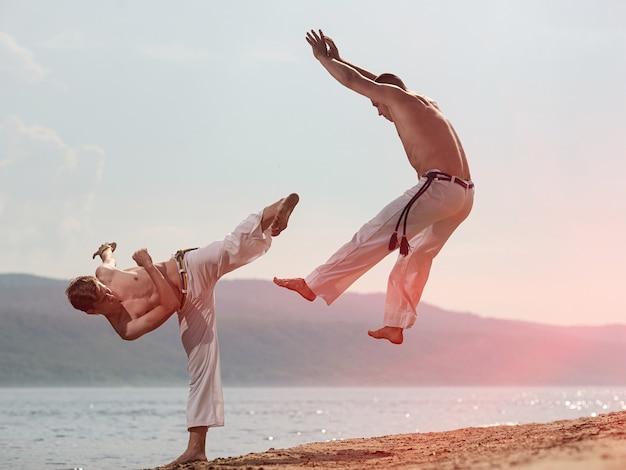 Mężczyźni trenują capoeira na plaży