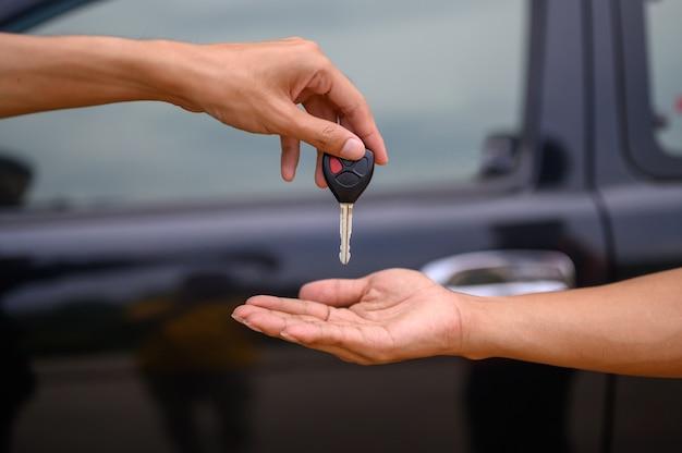Mężczyźni trzymają kluczyki do samochodu, aby poddać się personelowi, aby odebrać samochód.