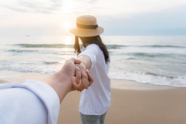 Mężczyźni, trzymając się za ręce kobiety na plaży, aby być szczęśliwym