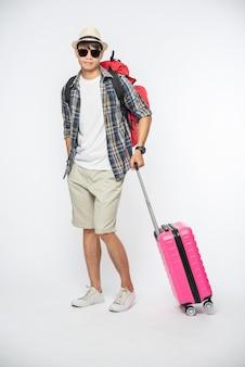 Mężczyźni ubrani do podróży, noszący okulary i kapelusze, noszący torby i bagaż