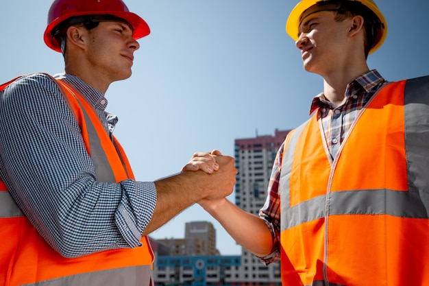 Mężczyźni ubrani w pomarańczowe kamizelki robocze i hełmy podają sobie ręce na budowie na tle wielopiętrowego budynku. .