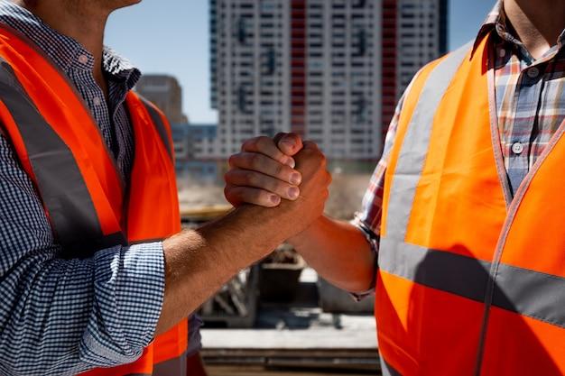 Mężczyźni ubrani w pomarańczowe kamizelki robocze podają sobie ręce na budowie na tle wielopiętrowego budynku. .