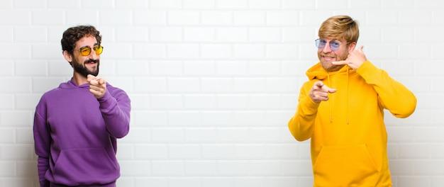 Mężczyźni uśmiechając się wesoło i wskazując na aparat, wykonując połączenie, gestykulujesz później, rozmawiając przez telefon