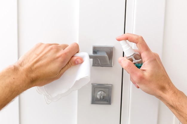 Mężczyźni używają papieru nasączonego alkoholem do przytrzymania gałki drzwi, aby zapobiec infekcji i wybuchowi wirusa covid 19. nie pozwól, aby covid dotknął drzwi.