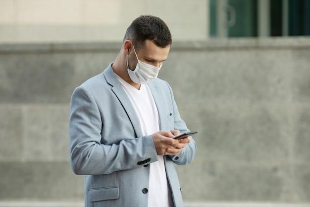 Mężczyźni używający telefonu w masce na ulicy