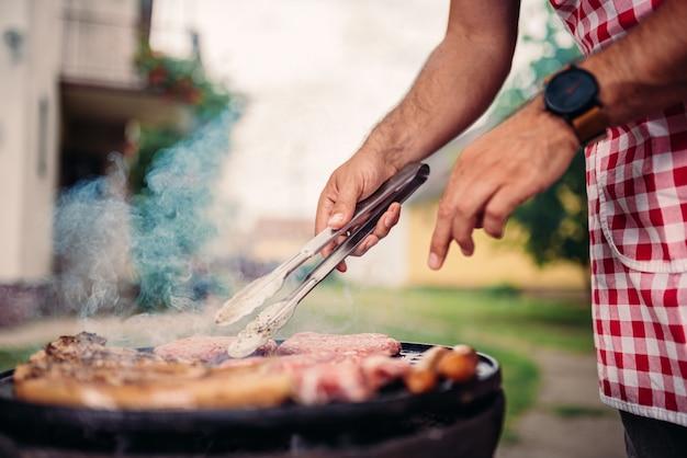 Mężczyźni w fartuchach grillujących mięso z kurczaka