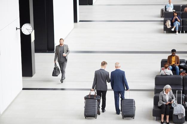 Mężczyźni w garniturach poruszający się po lotnisku