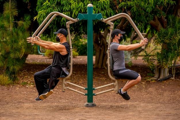 Mężczyźni w parku w maskach robiący maszynę sportową