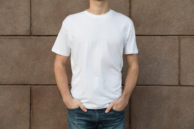 Mężczyźni w pustej białej koszulce przed budynkiem