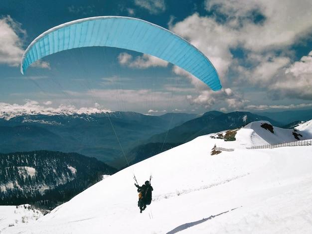 Mężczyźni w tandemowych paralotniach w zimowych, ośnieżonych górach i niebieskim tle nieba
