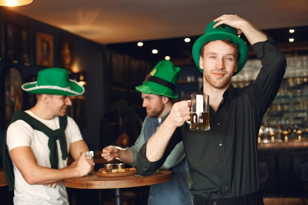 Mężczyźni w zielonych kapeluszach. przyjaciele obchodzą dzień świętego patryka. uroczystość w pubie.