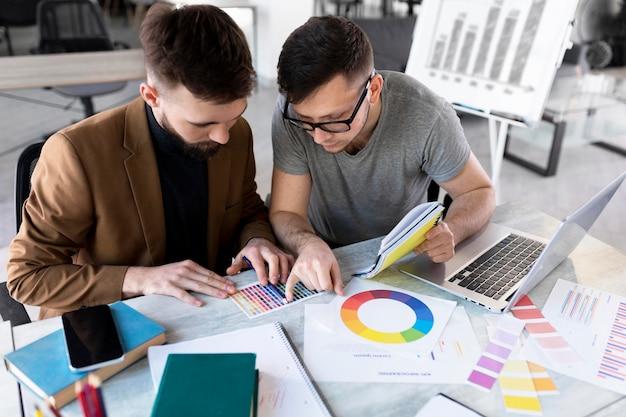 Mężczyźni wspólnie analizują wykres w pracy