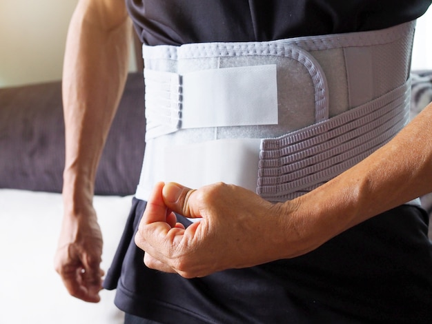 Mężczyźni z bólem pleców noszący pas podtrzymujący lub pas medyczny, ortopedyczne wsparcie lędźwiowe.