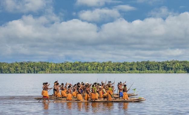 Mężczyźni z plemienia asmatów pływają w kajaku po rzece. amanamkay. wioska, prowincja asmat, indonezja