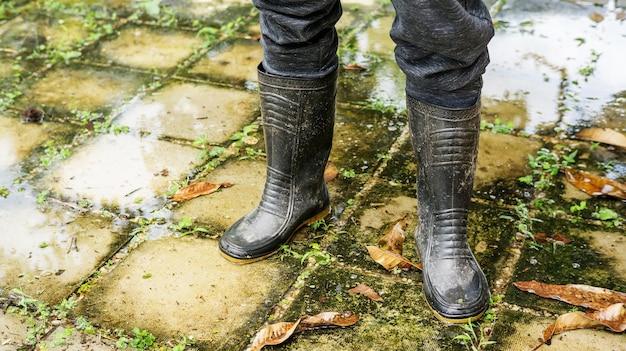 Mężczyźni zakładają czarne buty na wypadek powodzi.