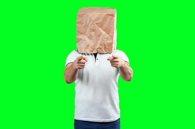 Mężczyźni zakładają na głowę papierową torbę, wskazują na ciebie palcem, motywują. izoluj na zielonym tle, obrazy można łatwo przycinać, aby używać w dowolnym miejscu, kopiować przestrzeń.
