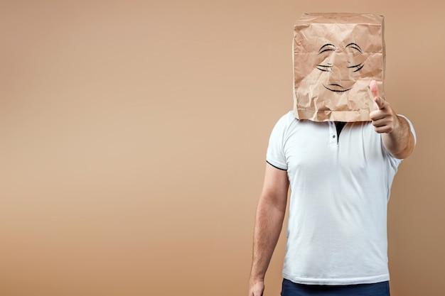 Mężczyźni zakładają na głowę papierową torbę z namalowanymi oczami, wskazują na ciebie palcem. izoluj na żółtym tle, obrazy można łatwo przycinać i używać w dowolnym miejscu, kopiować przestrzeń.