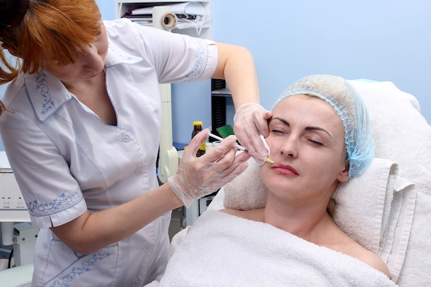 Mezoterapia. dorosła kobieta otrzymująca zabieg odmładzający w gabinecie kosmetycznym.