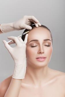 Mezoterapia igłowa. kosmetyk został wstrzyknięty w głowę kobiety. wzmocnić włosy i ich wzrost
