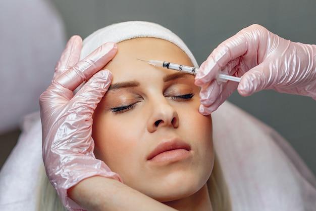 Mezoterapia. mistrz kosmetolog wykonujący zastrzyki odmładzające twarz w salonie.