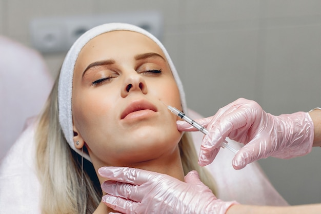 Mezoterapia. profesjonalna kosmetyczka mistrz wykonuje zabiegi kosmetyczne strzykawką na twarzy młodego klienta.