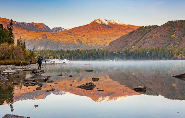 Mgła i mgła w świetle poranka na zewnątrz, unoszą się nad jeziorem kanas z drzewami liściastymi i alpejskim