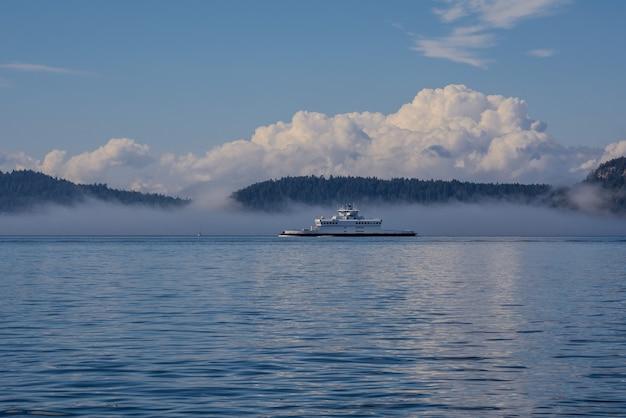 Mgła na oceanie, wyspy i morski prom są pokryte mgłą.